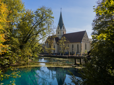 The well Blautopf in Blaubeuren, Germany with a church in the backgrund