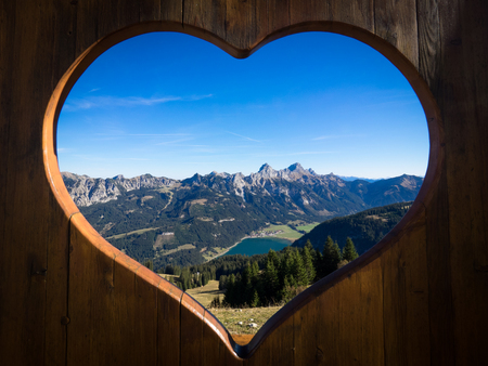 Tannheimer Tal panorama with view on the Haldensee seen through a wooden heart 版權商用圖片