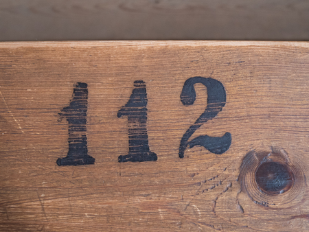 Number 112 on wooden surface
