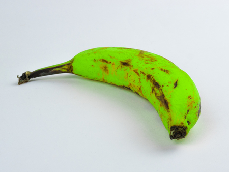 Green neon colored banana on white background