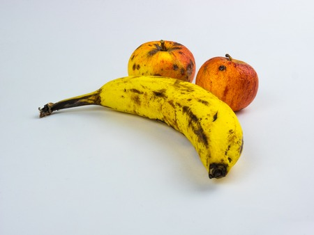 Overripe banana with apples on white background