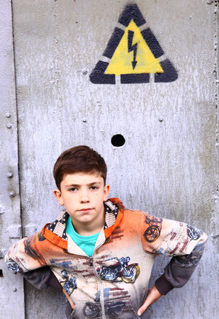 waif: preteen handsome boy on front of the door with electricity warning sign