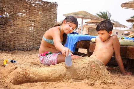 petit bonhomme: frères et s?urs préadolescence frère et la s?ur ont du plaisir sur le jeu sable de la plage de sable