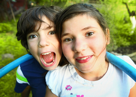 country girls: siblings preteen boy and girl together close up portrait on the summer green background Stock Photo