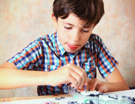 adult boys: preteen handsome boy make hand made toys from rubber band rainbow loom