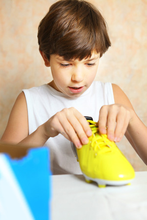 preteen boys: preteen handsome boy with brand new yellow footbal boot as a birthday present