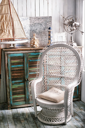 dining table and chairs: sea travel styled shabby chic interior corner with map wicker chair ship and shell Stock Photo