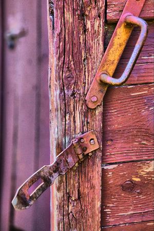 doorhandle: old cracked country door surface with iron bolt catch lock and door-handle