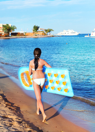 preteen girl in swimming suit with inflatable matress on the blue sea with yacht background Stock Photo
