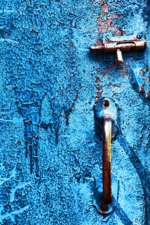 doorhandle: old cracked country blue door surface with iron bolt catch lock and door-handle