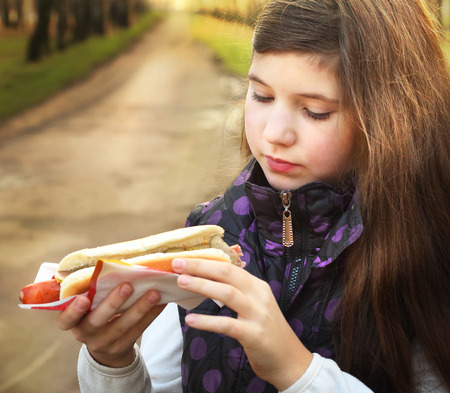 hungry children: beautiful preteen girl with long dark hair eat hot dog in the spring sunny park