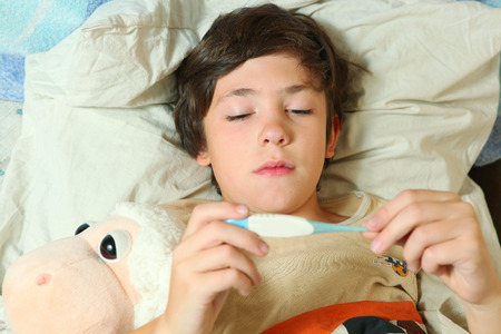 handome: sick preteen boy in bed with termometer show high temperature Stock Photo