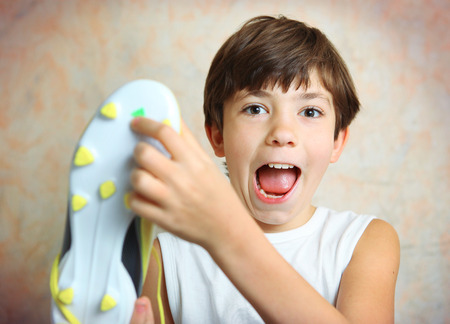 football boots: teen handsome boy with brand new yellow football boots close up photo