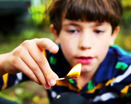 preteen knappe jongen spelen met vuur greep match Stockfoto