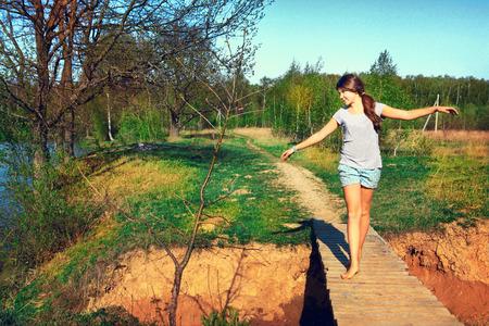 tiener mooi meisje lopen op de houten brich van het land zomer achtergrond lake Stockfoto
