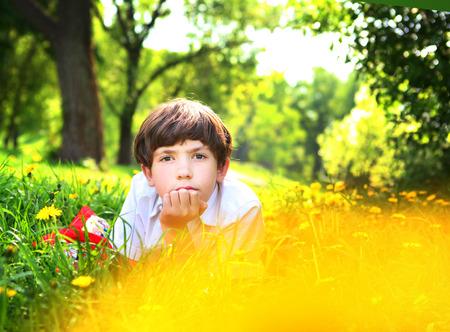 Prodigy: preteen przystojny chłopak z poważną miną leżał śni na letnim parku wśród kwiatów mniszka lekarskiego Zdjęcie Seryjne