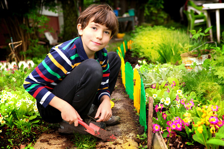 preteen handsome boy work in the blossoming summer garden