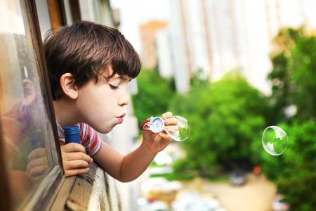 ragazze bionde: preteen bel ragazzo con le bolle di sapone lood fuori dalla finestra