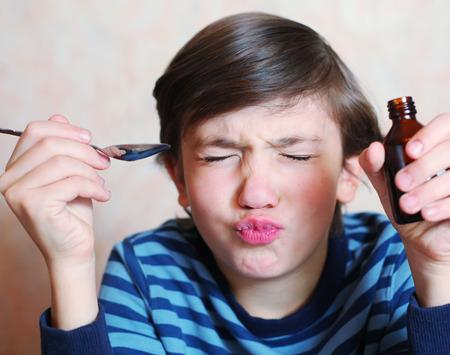 doses: preteen knappe jongen maakt een grimas na het nemen van bittere geneeskunde
