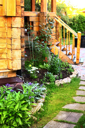 path cottage garden: wooden cottage house porch and tile path in the summer blossoming garden