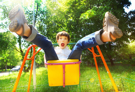 preteen boys: preteen handsome boy swinging on the swing in summer sunny day