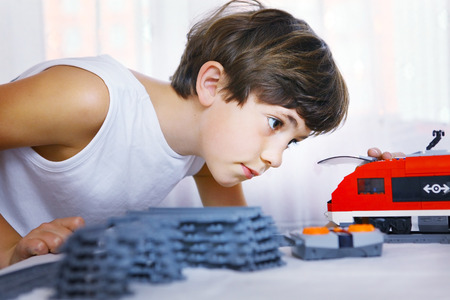 handsome boys: preteen handsome boy play with meccano toy train and railway station Stock Photo
