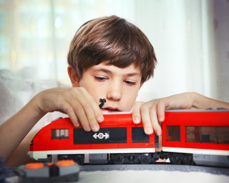 play boy: preteen handsome boy play with meccano toy train and railway station Stock Photo