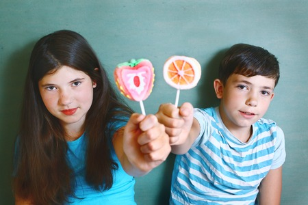 mellow: happy couple siblings boy and girl  with fruit designed marsh mellow candies on stick