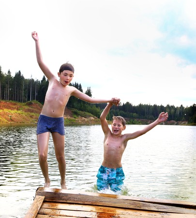 ponton: two  boys jump in lake on summer hot day