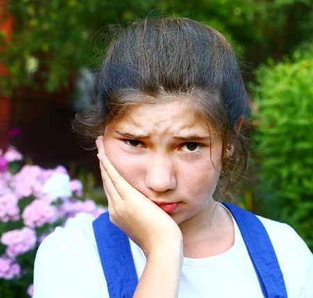 pretty girl with toothache outdoor summer portrait