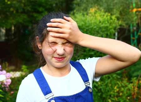 sunstroke: teenager  pretty  girl suffering from  severe headache