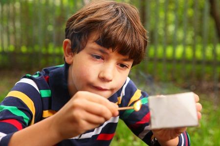 cerillos: chico guapo preadolescente jugar con la caja de cerillas Foto de archivo