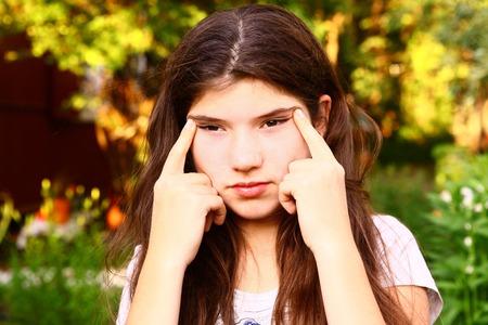 myopia: teen girl  with myopia try to see something far away Stock Photo