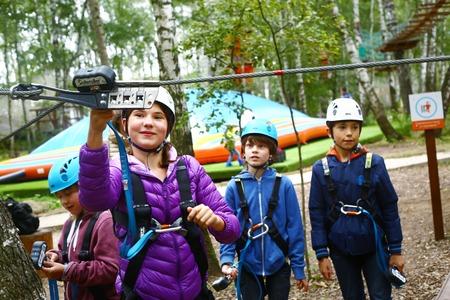 Los niños en el equipo safaty tienen instrucciones antes de pasar la ruta de escalada difícil Foto de archivo - 50974387