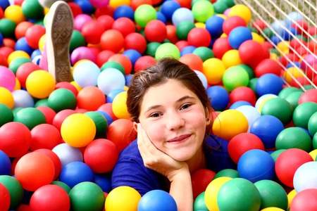 color balls: teen beautiful girl in color balls pool Stock Photo