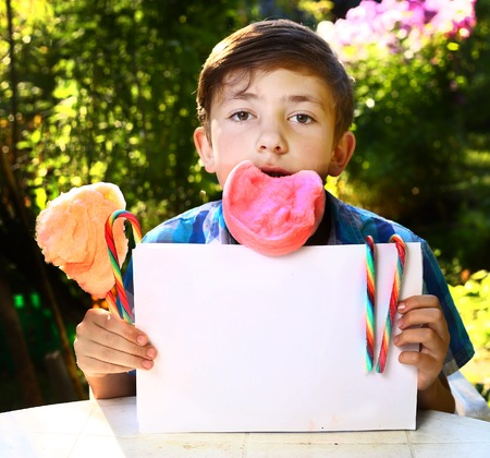 candy floss: boy with  cotton candy and sheet of paper on the summer garden background