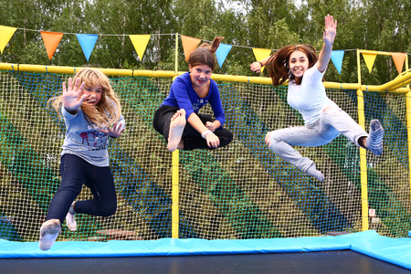 indoors: Three  girls jump on trampoline  in special park for sport activities in Moscow  Russia