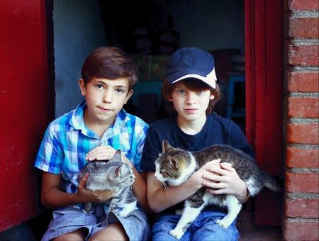 jongens met katten op de knieën zitten op het huis veranda Stockfoto