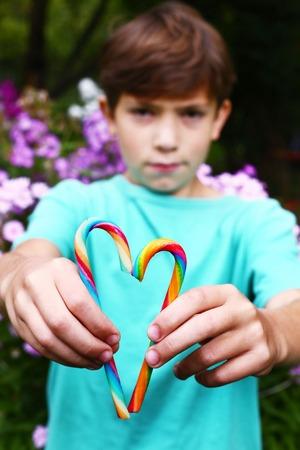 preteen boys: preteen boy with rainbow candy sticks on the summer blossom garden background Stock Photo