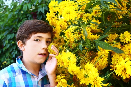preteen boys: handsome boy with yellow big flowers close up portrait Stock Photo