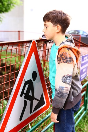 waif: preteen handsome boy at the construction border with warning sign Stock Photo
