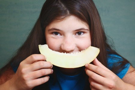 beautiful preteen girl: preteen beautiful girl with long dark hair with slice of melon isolated on blue background Stock Photo
