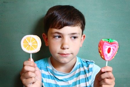 preteen boys: preteen handsome boy with two marshmellow sweets on stick isolated on blue