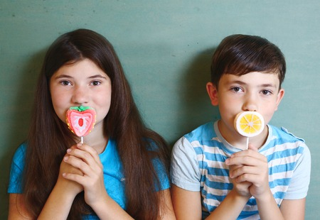 fruit candy: brother and sister with fruit candy on stick isolated on blue Stock Photo