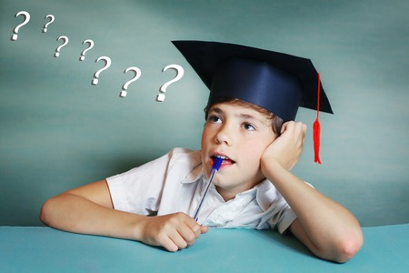 to think about: preteen handsome boy in graduation cap think about school subject