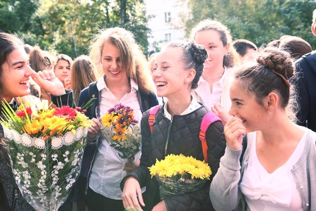 grade school age: MOSCOW, SEPTEMBER 1, 2015: Unidentified teen girls with flowers celebrate their first school day at September 1, Moscow Russia