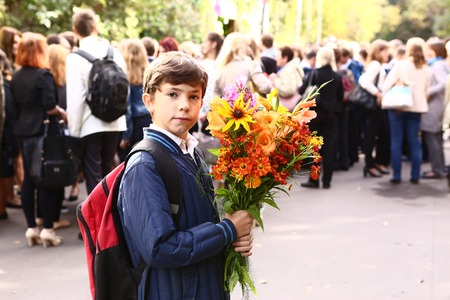first day: MOSCOW, SEPTEMBER 1, 2015: Unidentified boy with flowers celebrate first school day at September 1, Moscow Russia