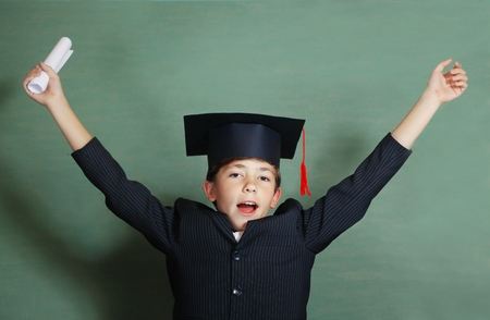 prodigy: preteen boy in business suit and graduation cap cheer about coming holiday