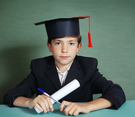 prodigy: boy in  graduation cap close up portrait isolated on blue