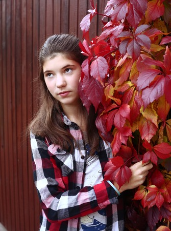 difficult period: teen girl with long brown hair sad portrait on the autumn fall background Stock Photo